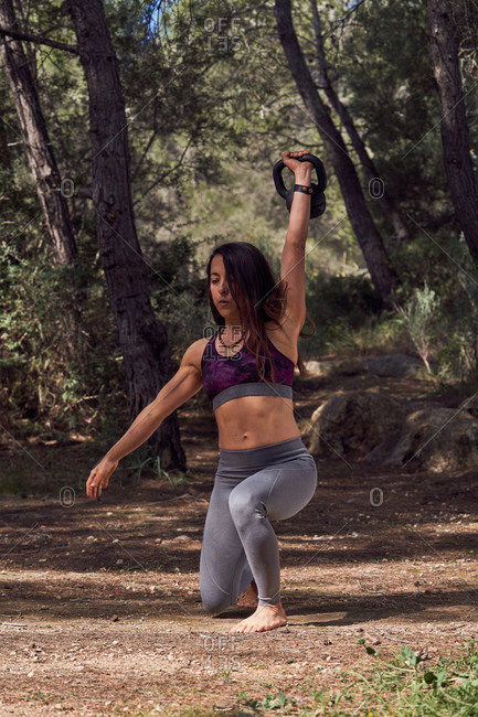 Sportive female in sports clothes doing push up with kettlebell from starting position of squat on the alley of picturesque park