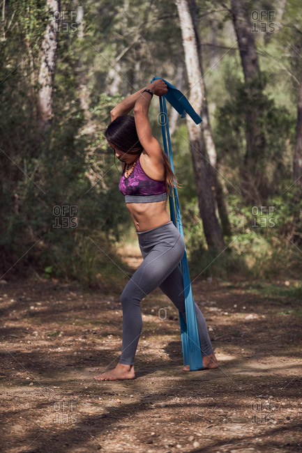 Full body of young female in sportive clothes doing squats while working out with fitness rubber band fixed on tree in nature