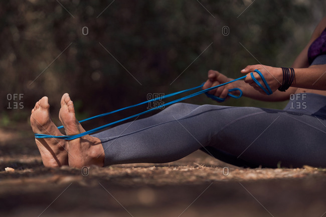 Close up view of sportswoman in activewear doing workout while sitting on ground while pulling tubular expander training abs and biceps in nature on sunny day