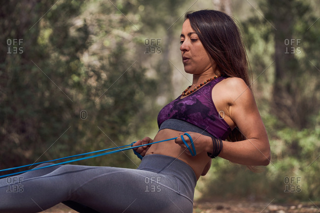 Young sportswoman in activewear doing workout while sitting on ground while pulling tubular expander training abs and biceps in nature on sunny day