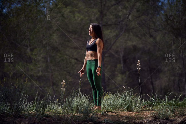 Slim female athlete in leggings and top enjoying morning sun after intensive workout in sunny park