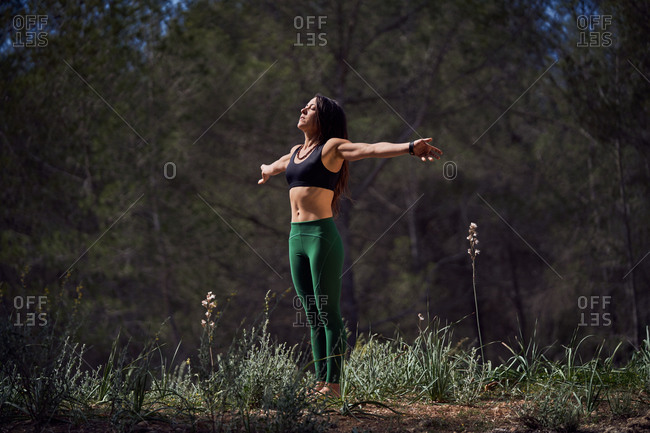 Slim female athlete in leggings and top spreading arms apart while stretching shoulders and enjoying morning sun after intensive workout in sunny park