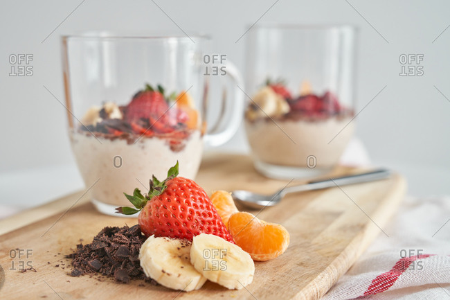 Glass mugs of delicious fresh yoghurt decorated with strawberry with chocolate and pieces of banana and tangerine placed on wooden cutting board on gray background