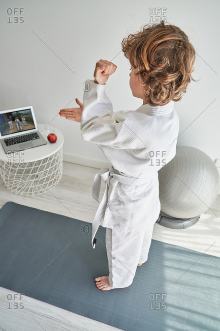 From above view of young boy with curly hair in white kimono standing on mat in front of laptop at home and learning hands position in judo