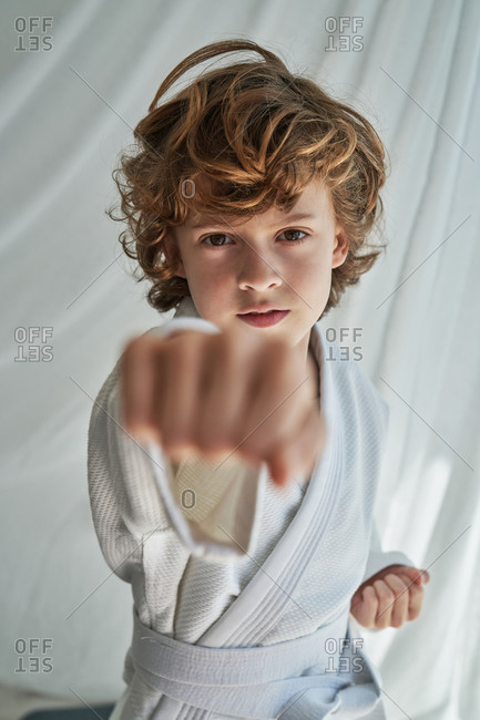 Positive focused young boy with curly hair wearing white kimono and tightening belt while practicing judo in light room looking and throwing a punch towards the camera at home