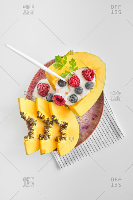 From above pieces of ripe papaya with yoghurt and fresh berries placed near spoon on plate on white background