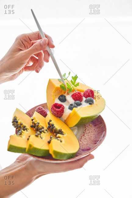 Unrecognizable person carrying plate with fruit dessert and poking slices of papaya with yoghurt and berries with stick against white background