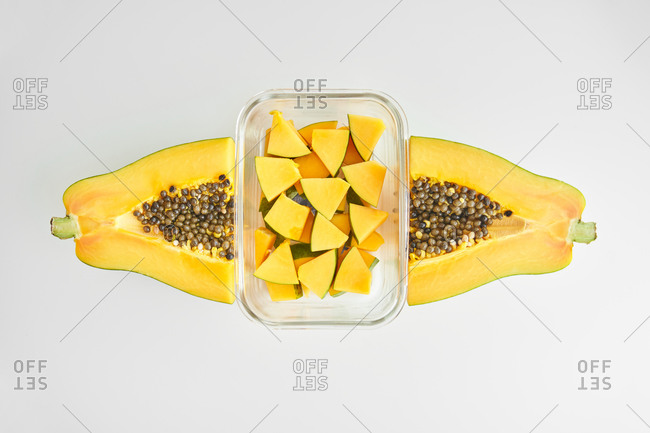 Top view of halves of ripe papaya and glass container with pieces of fresh fruit placed on white background