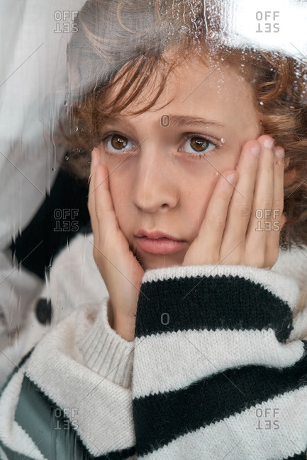 Bored boy with hands on cheeks looking out wet window while resting at home on rainy day