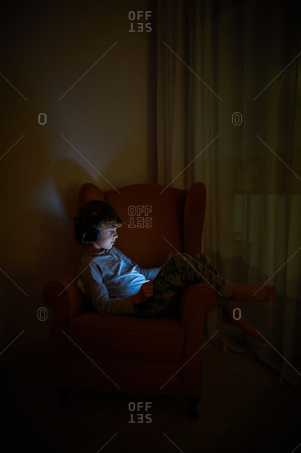 Stock vertical photo of a child sitting on an armchair in a corner of a room looking at tablet computer with headphones at night. Technology