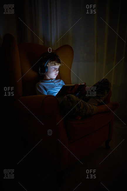 Stock vertical photo of a child sitting on an armchair in a corner of a room with a tablet in his lap with headphones at night. Technology