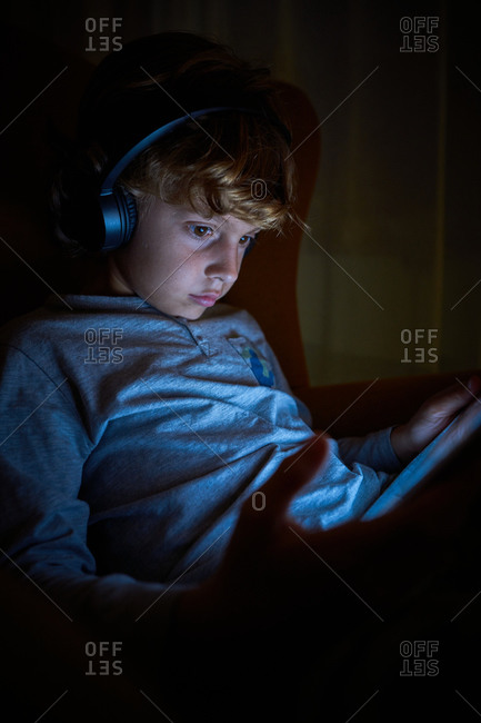 Stock vertical photo of a child sitting with headphones on a sofa with a tablet at night. Technology