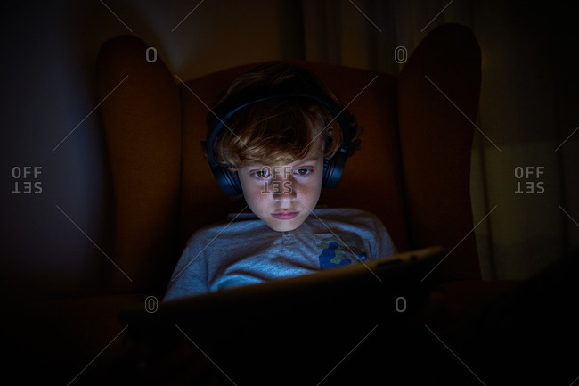 Stock photo of child sitting with headphones on a sofa looking at the tablet at night