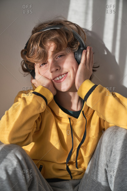 Pleased child in headphones and yellow sweater and gray pants sitting looking at camera and listening to song while relaxing alone at home