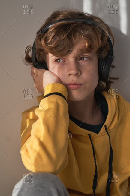 Thoughtful child in headphones and yellow sweater and gray pants sitting looking away and listening to song while relaxing alone at home