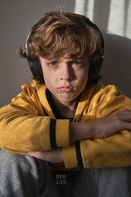 Thoughtful child in headphones and yellow sweater and gray pants sitting looking at camera and listening to song while relaxing alone at home