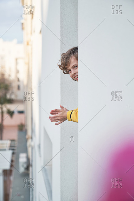 Through blurred pink flowers view of little kid clapping hands out window looking at camera while chilling on balcony of modern apartment of multistory building in city