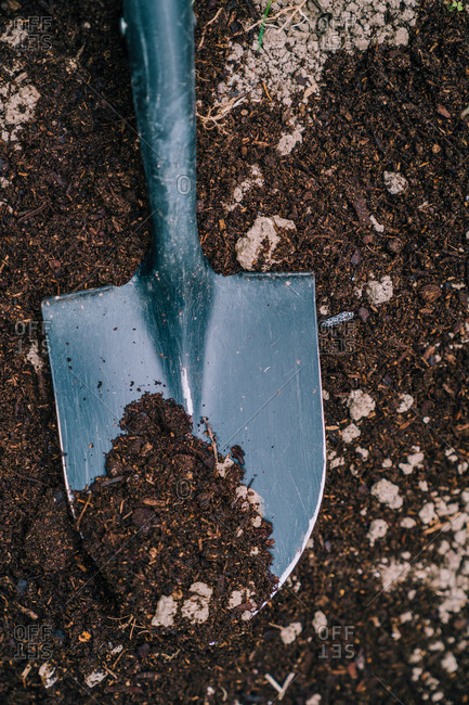 From above of metal garden shovel with soil digging ground in sunny garden in countryside