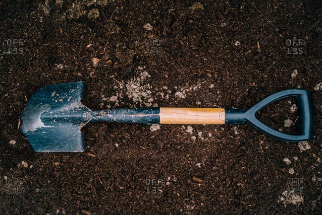 Shovel with soil in garden