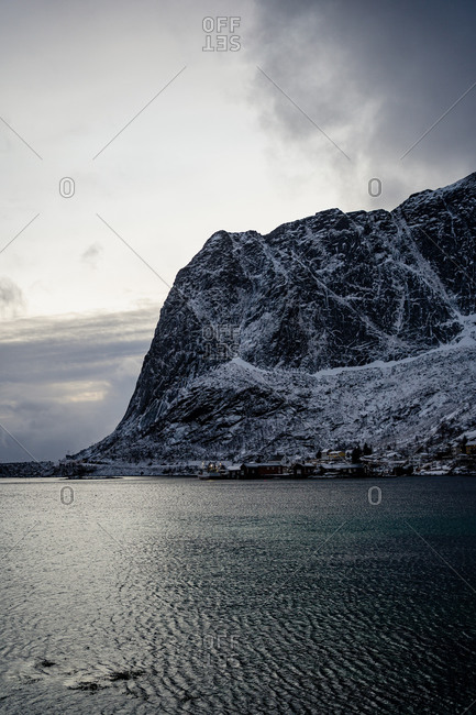 From above of city harbor against snowy mountain ridges at horizon in overcast weather in Norway