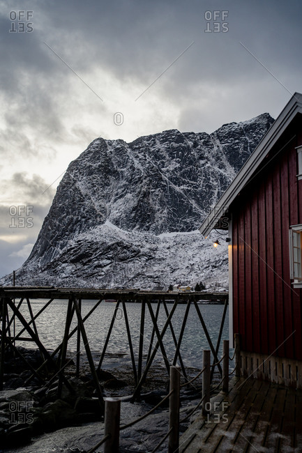 Cottage with red striped walls and white window frames on wooden pier on strait shore against snowy township at foothill in winter cloudy day in Lofoten
