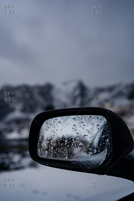 Wet side rear view mirror of modern black auto with melting snow against blurred snowy highland under gray cloudy sky in winter Norway