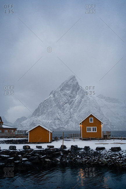 Snowy orange country houses on coast of strait with rippled water in cold overcast weather in Lofoten