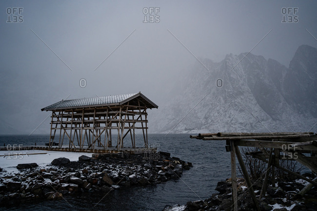 Solitary construction with wooden pillars and gray roof on stone beach washing by troubled water against misty mountain ridges in overcast weather in harbor in Norway