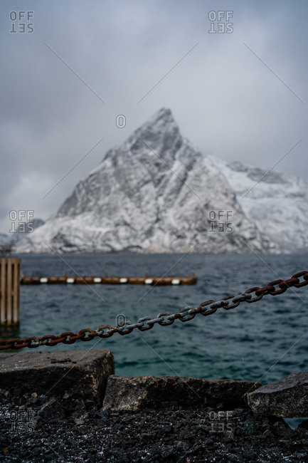 Stone embankment with chain fence and barrier against rippled water of strait washing coast with snowy mountain in winter overcast weather in Norway