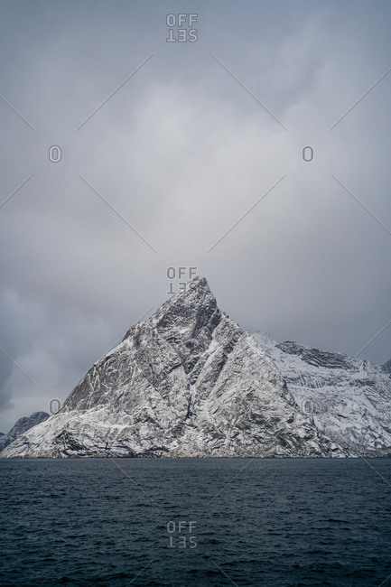 Breathtaking view of blue rippled sea water against snowy mountain ridges on shore under gray cloudy sky in wintertime in Norway
