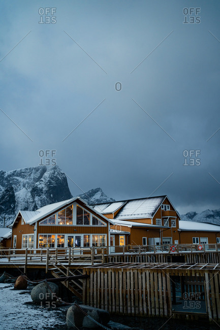 Yellow country houses on coast of strait against misty snowy mountain crests in overcast weather in Norway