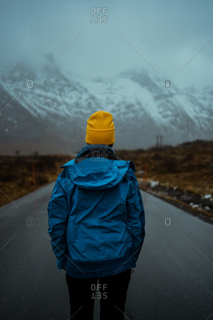 Back view of relaxed unrecognizable person in blue warm clothes and bright yellow beanie hat standing on asphalt road going to snowy foggy mountains in Lofoten