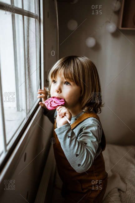Adorable little girl in casual clothes sucking sweet lollipop and looking out window while resting in cozy room at home