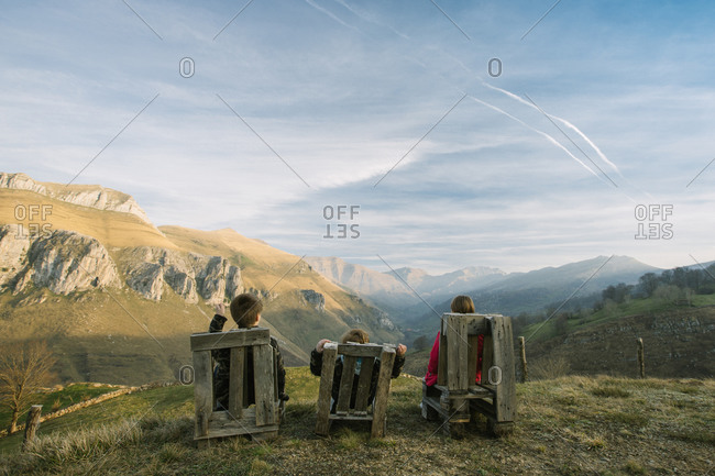 children in casual clothes sitting on wooden benches on remote green hill and enjoying view while visiting Spain