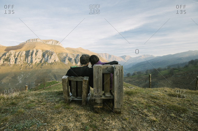 Couple sitting on wooden benches on remote green hill and enjoying view while visiting Spain