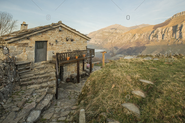 Old stone house with tiled roof and with wooden terrace located in rocky terrain in Cantabria