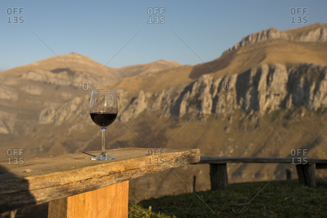 Transparent glass of red wine placed on wooden table on remote green meadow in countryside with view of mountains in Cantabria