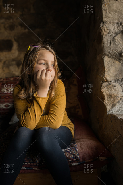 Lonely thoughtful girl in casual clothes leaning on hand while sitting on couch and looking away in window of old stone house in Spain