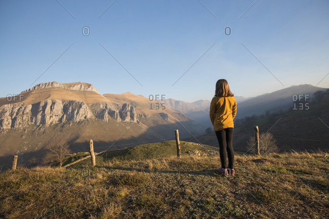 Back view of faceless girl in casual clothes standing alone on green hill and enjoying picturesque view of mountains and sky in Cantabria