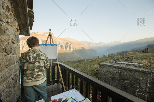 Anonymous boy painting at easel on sunny terrace in countryside of Spain