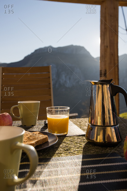 White cups and hot coffee maker placed on table with hot toast and glass of fresh orange juice on outdoor veranda with mountain on background