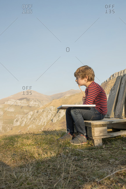 Side view of adorable child sitting on wooden bench and painting on canvas during weekend on background of magnificent mountainous landscape