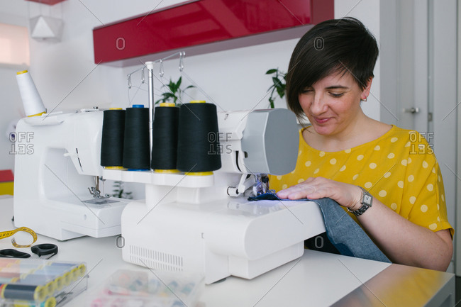 Happy brunette adult woman smiling and using sewing machine to make denim garment while working in home workshop