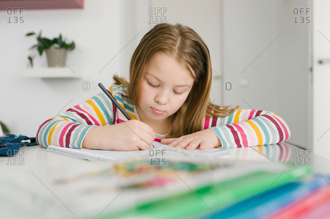 Focused girl in striped t shirt writing in notebook while sitting at table and doing homework at home