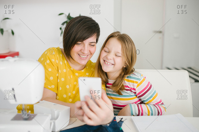Cheerful adult woman smiling and taking selfie with girl while sitting at table and working in dressmaking workshop at home