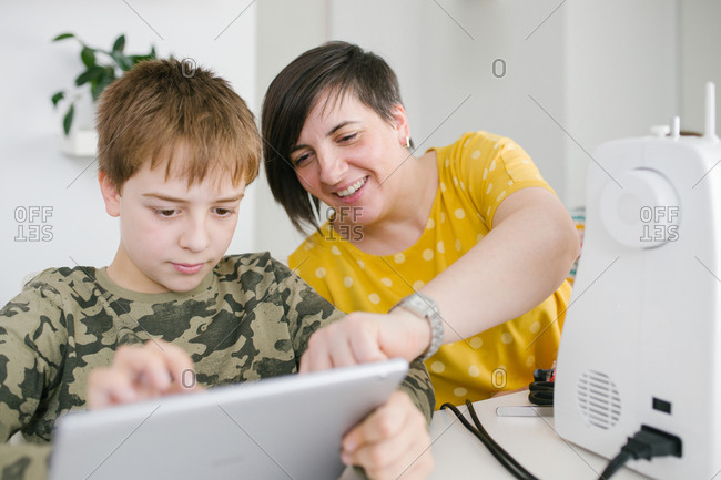 Adult woman helping little boy browsing modern tablet together while sitting at table at home