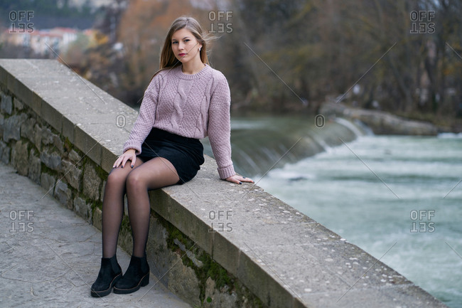 Peaceful lady wearing knitted sweater and short black skirt and sitting on stone fence while having walk close to river