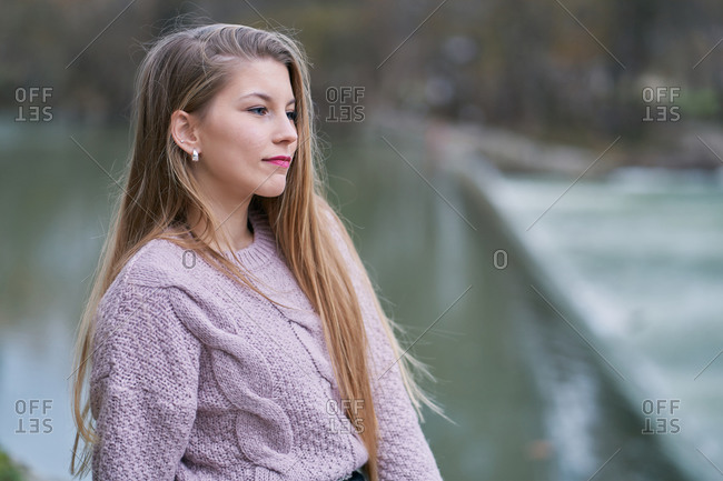 Pensive blond woman wearing light purple sweater looking away against blurry background