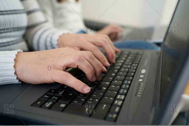 Side view of anonymous woman in casual clothes typing on laptop keyboard while working on freelance work at home