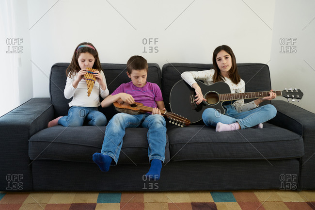 Positive young little boy and girls in casual clothes sitting on comfortable sofa together and playing music instruments while spending time together at home